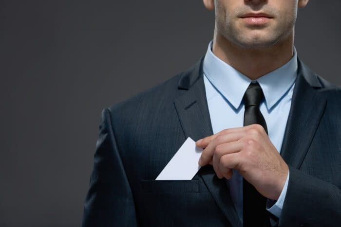 Part of body of man who pulls out business card from the pocket